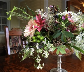 Mercury glass pedestal vase holds a mix of seasonal flowers